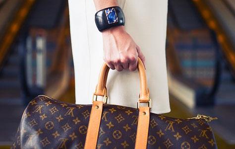 Prim-plan cu mana unei femei tinand o geanta Louis Vuitton